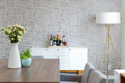 A dining space with brown and white wallpaper.