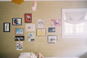 Grass-cloth wallpaper decorated with children's artwork
