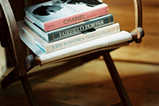 A stack of books on a wooden folding chair