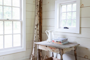 A windowed corner features a rustic table and slim birch logs