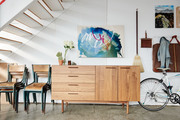 An entryway with a bike and a hanging abstract painting.