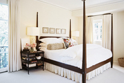 A wooden four-poster bed outfitted with white scalloped bed linens