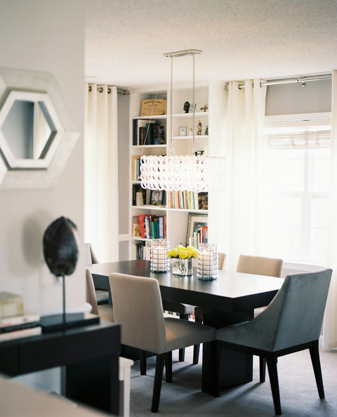 Dining Room - A glass chandelier suspended above a wood table and a mixture of white and gray dining chairs