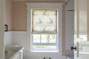 A bathroom with orange wallpaper, subway tile, and window with a patterned roman shade