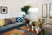 A family space filled with a blue couch and a pair of striped armchairs