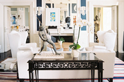 A black console table and white furniture atop a striped rug