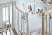 A wall of dog art above a staircase