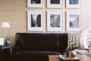 A grid of black-and-white artwork above a leather couch