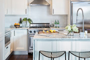 White cabinetry and stainless steel appliances in marble counter-topped kitchen.