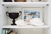 White shelves holding seashells, decorative accessories, and books