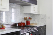 Black lower cabinets, range, and hood offset by marble countertops and backsplash, plus white upper cabinets