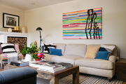 Large-scale art above a big cozy sofa with patterned throw pillows.