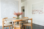 A contemporary dining space with abstract art and mid-century style dining chairs.