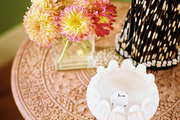 Flowers and decorative accessories on a carved-wood side table