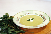 A bowl of minted pea soup atop a wooden tray in a kitchen with marble countertops