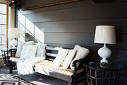 A sunporch with a black bench, a patterned rug, and a pair of white lamps