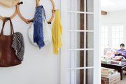 An entryway with a coat rack and a bin for shoes