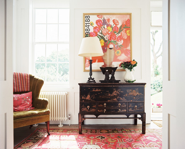Entry - A black chinoiserie cabinet beside a channel-back armchair