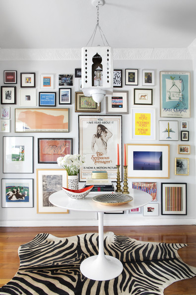 Entry - A gallery wall making a backdrop for a Saarinen table on a zebra rug