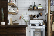 A reclaimed wooden bar in a whitewashed kitchen with subway tile and dark grout.