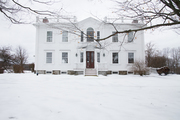 The exterior of a traditional white home in winter.