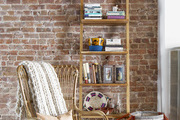 A Bohemian chair in a Brooklyn living room lined with brick walls.