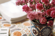 A vase of flowers on a colorful tabletop