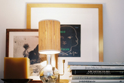 A stack of books, framed art, and a mirrored lamp on a shelf
