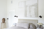 Large scale art hanging above brown bed.