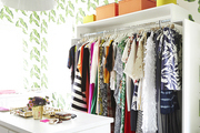Clothing rack and other storage in bright  walled room.
