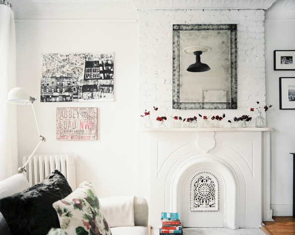 Fireplace - A mirror above a mantel in a living space with a white floor lamp and a linen couch