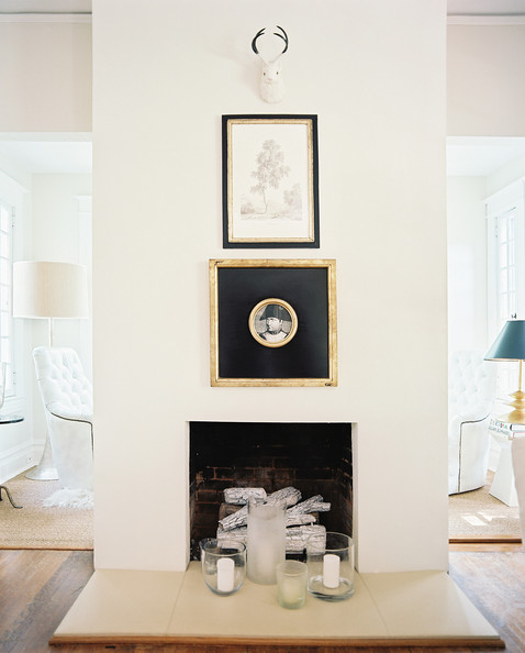 Fireplace - A white mantel adorned with framed art