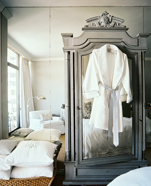 French Closet - A gray mirrored armoire against a wall of mirrors