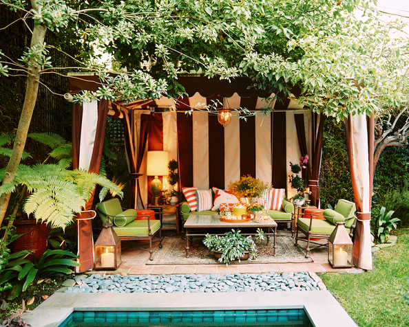Furniture - A striped cabana and green patio furniture in an outdoor living space
