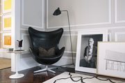 A living room corner with a black-and-white portrait of David Hockney next to an Ed Ruscha etching