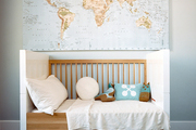A world map above a white-and-wood convertible crib