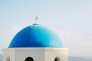 A domed building with the ocean as a backdrop