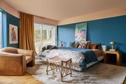 Jewel-toned main bedroom with textured rug and leather furniture.
