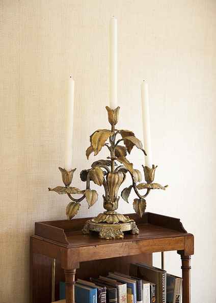 Gold Bookshelf - A gilded candelabra on an antique wood side table