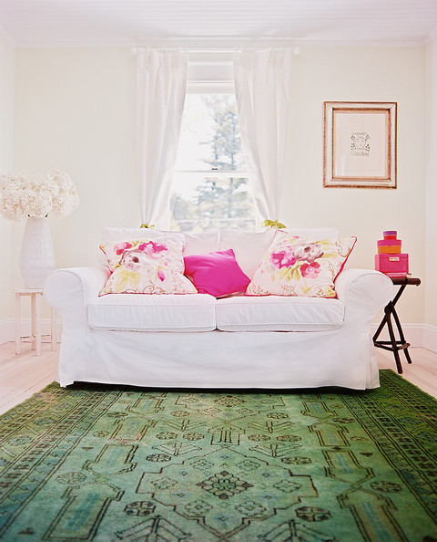Green Living Room - A white slipcovered sofa with floral pillows sits on top of an overdyed green rug in an English-country-style room.