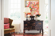 A black chinoiserie cabinet beside a channel-back armchair