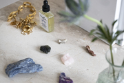 Crystals, gold jewelry, and essential oil on a ledge.