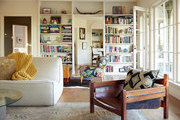A living room with midcentury furnishings and floor-to-ceiling bookcases