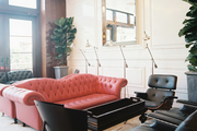 A red tufted couch surrounded by black chairs