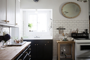 A whitewashed kitchen with subway tile and dark grout.