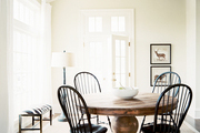 Black Windsor dining chairs surrounding a round wooden table