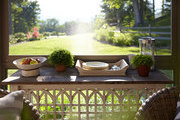 A sideboard hosting a tray of basic serving utensils and plates on a screened-in porch