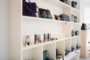 Colorful handbags and accessories on white shelves