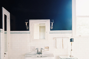 Greek-key tile borders in a bathroom with white subway tile and black walls