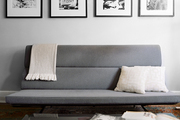 Black-and-white photography above a gray couch and a glass-topped coffee table